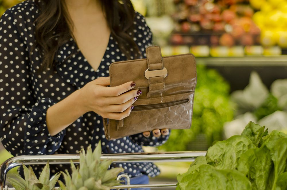 Young woman opening wallet at the supermarket; Shutterstock ID 100487089
