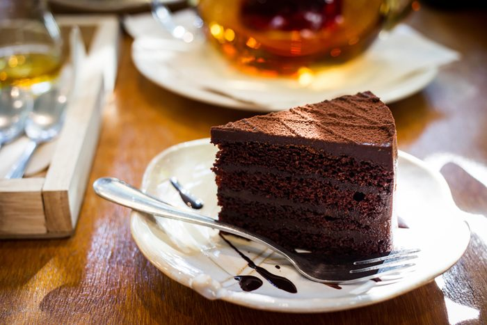 A piece of dark chocolate cake with a fork and tea