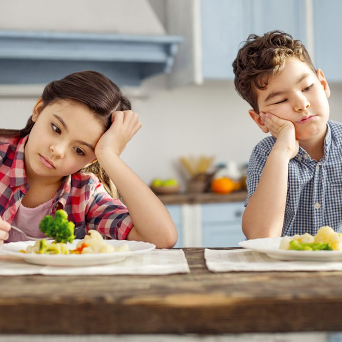 Sad dark-haired little brother and sister sitting at the table and having healthy breakfast and looking sadly at the vegetables