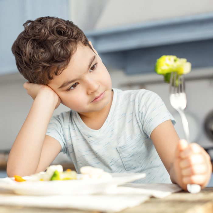 Handsome sad dark-haired little boy having healthy breakfast and looking at the green vegetable on his fork and not liking it