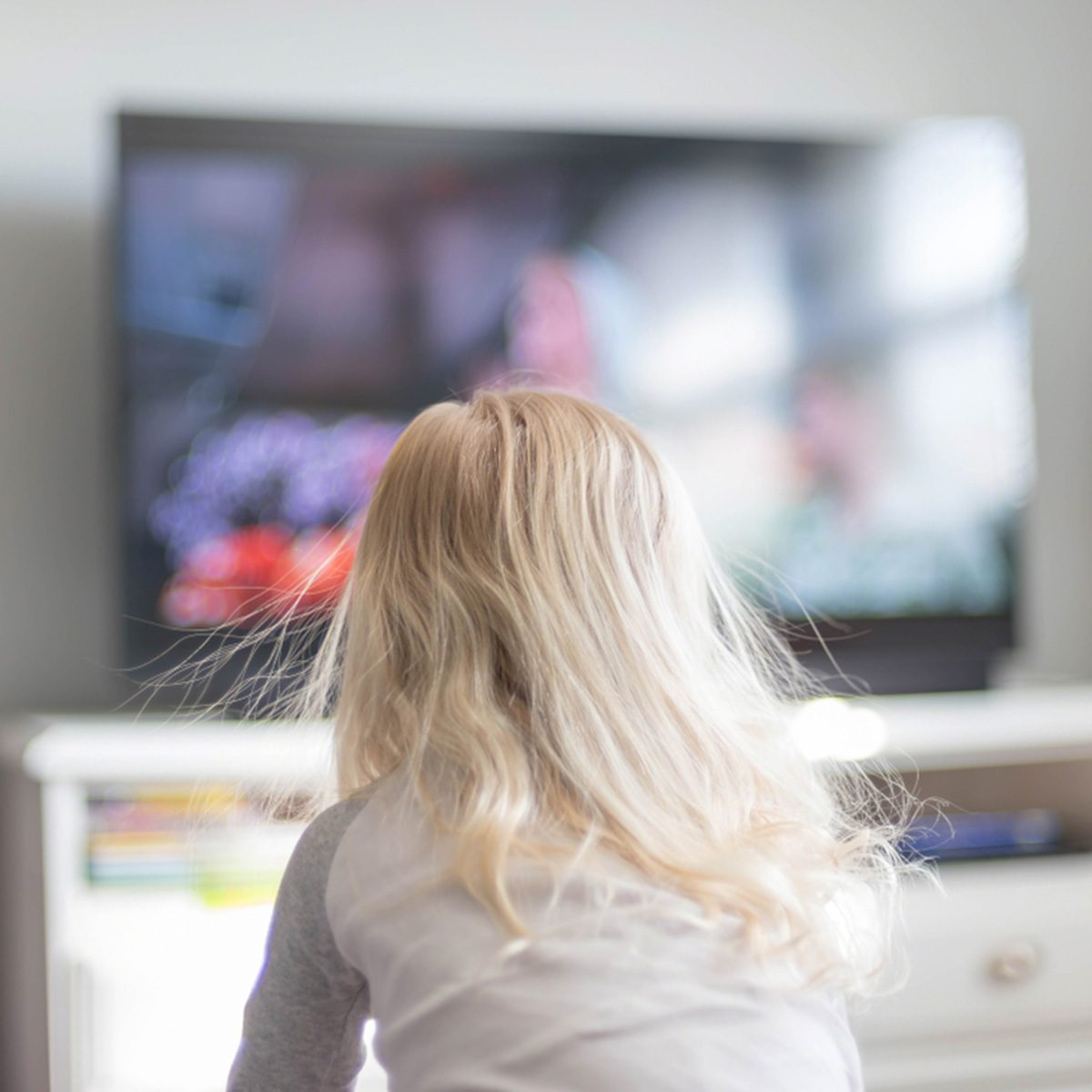 Blonde haired girl with static electricity watching TV in morning sunlight; Shutterstock ID 1043650873; Job (TFH, TOH, RD, BNB, CWM, CM): Taste of Home