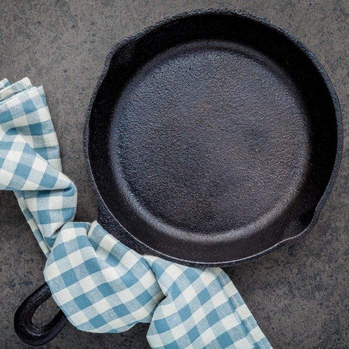 Empty cast iron skillet frying pan flat lay on dark stone background