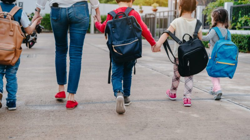 Mother and pupil and kids holding hands going to school in first class with schoolbag or satchel walking to school bus