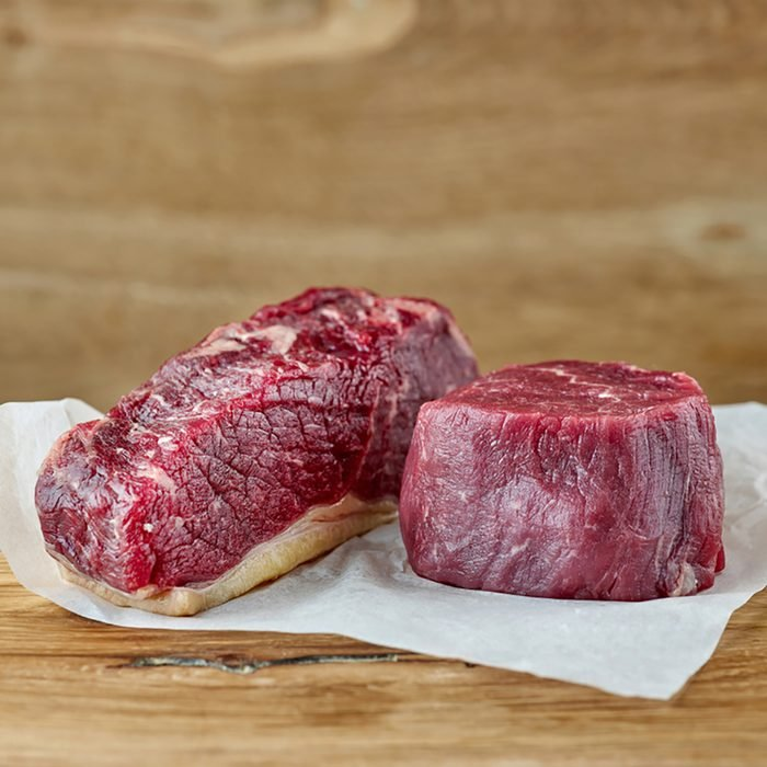 raw strip loin and fillet mignon steak on wooden table