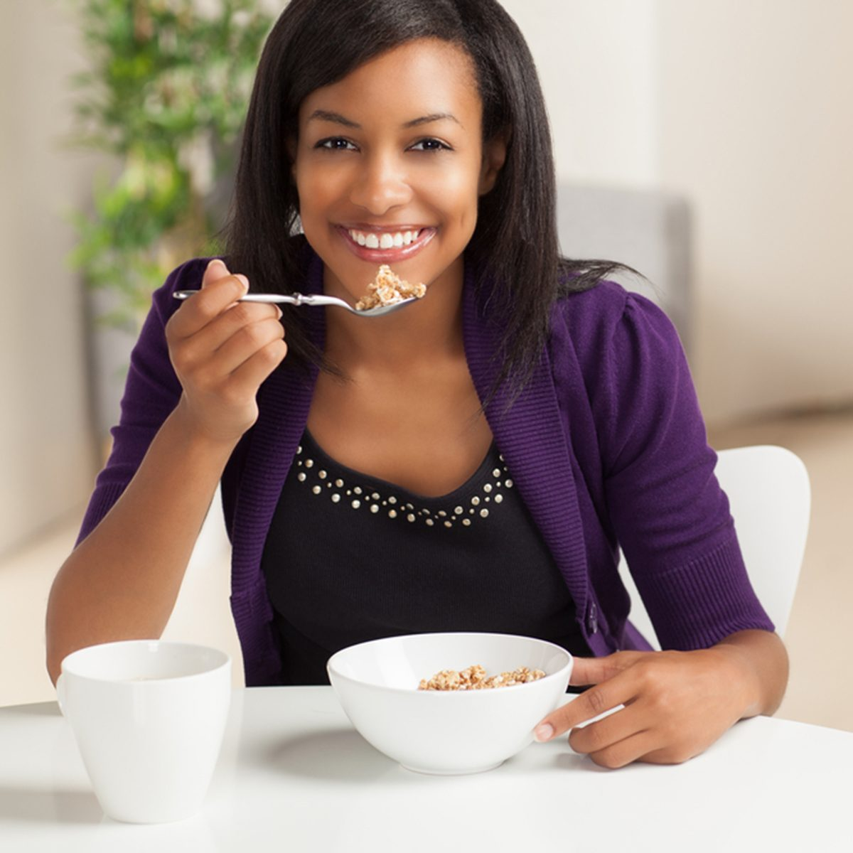 Beautiful young black female sitting at dining room table eating breakfast and drinking coffee.