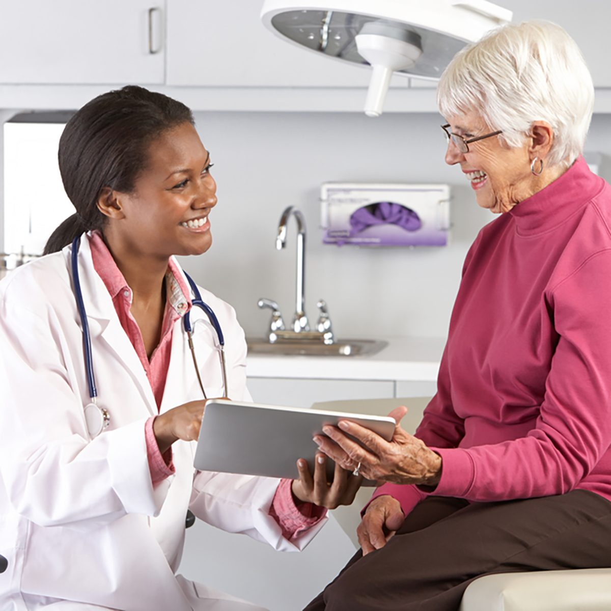 Doctor Discussing Records With Senior Female Patient;