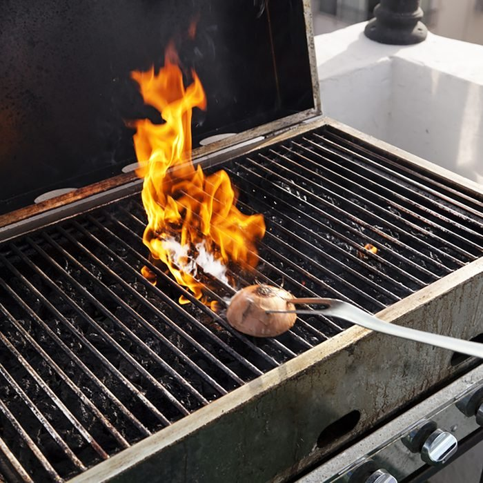 Getting the grill ready for some cooking - rubbing halved onion on the hot grate.
