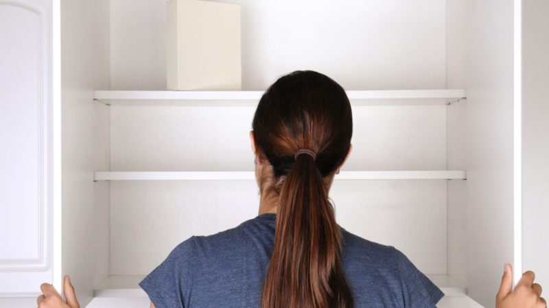 Closeup of a woman looking in an empty pantry.