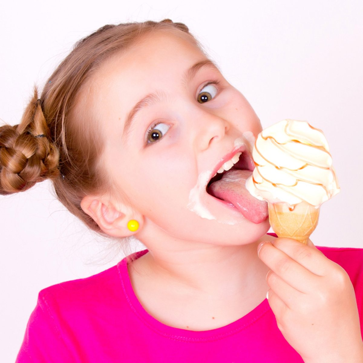 A head portrait of a beautiful smiling caucasian girl child eating a delicious white vanilla ice-cream