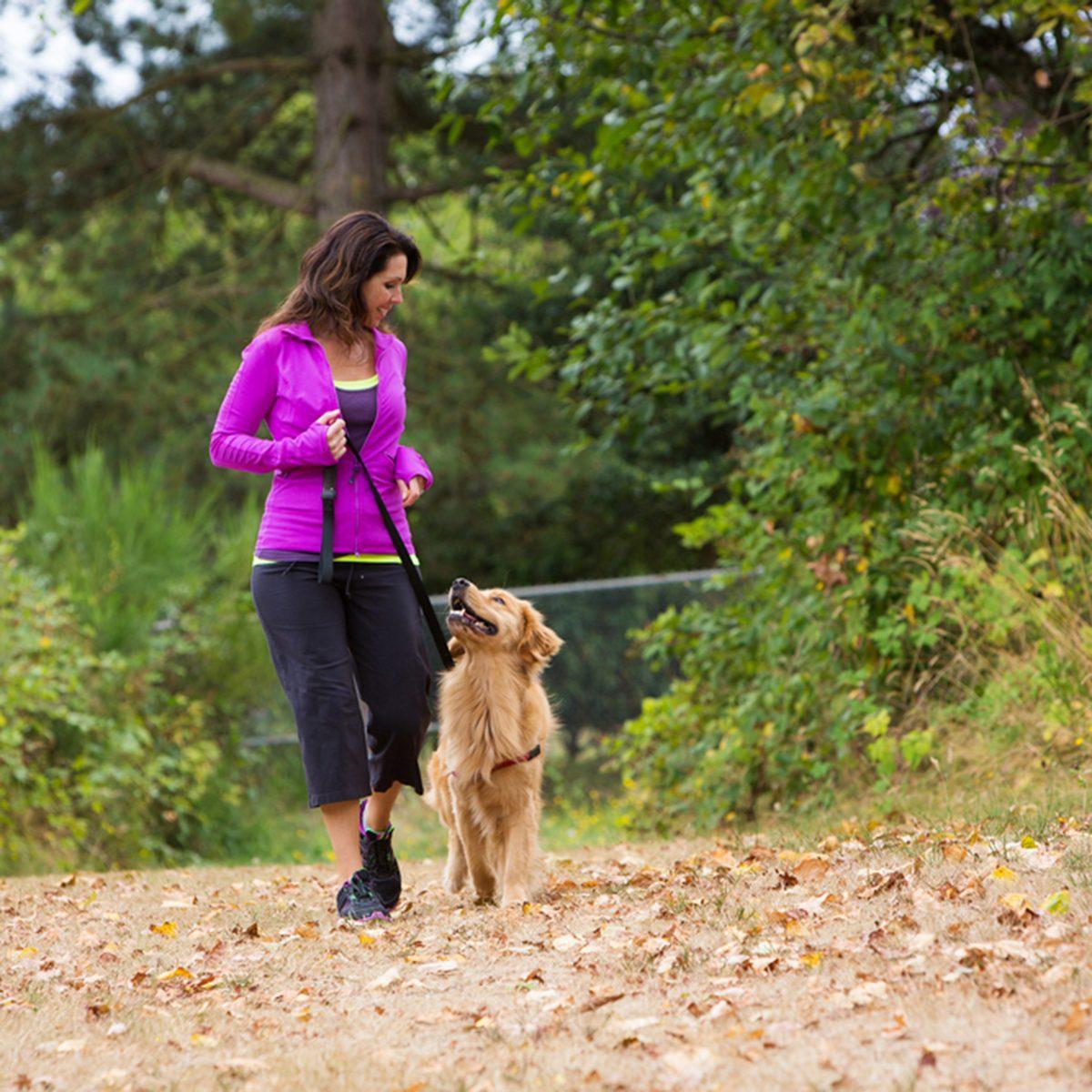 A pretty woman walking her dog