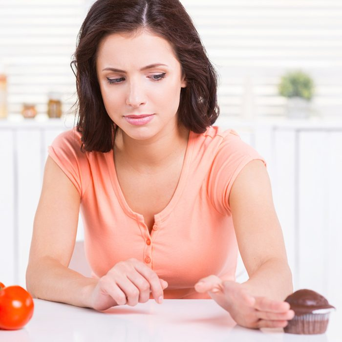 Say no to unhealthy food! Confident young woman putting away chocolate muffing laying near the fresh vegetables
