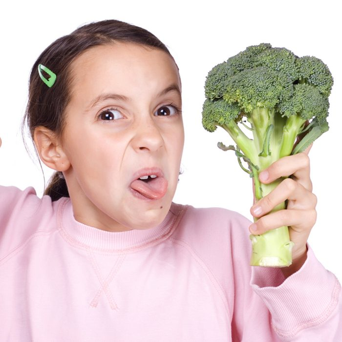 Young girl holding a broccoli isolated on white