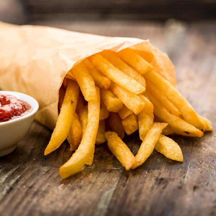 Fresh fried french fries with ketchup on wooden background