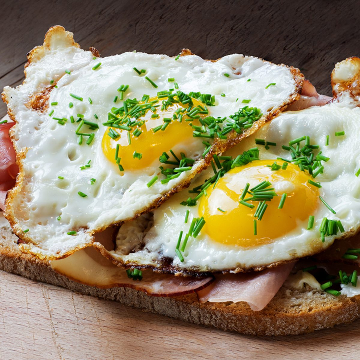 Slice of rustic bread with ham or bacon and fried egg