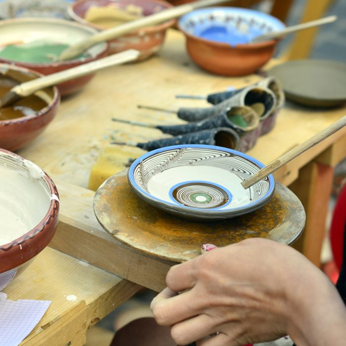 Woman painting traditional plates at a fair.