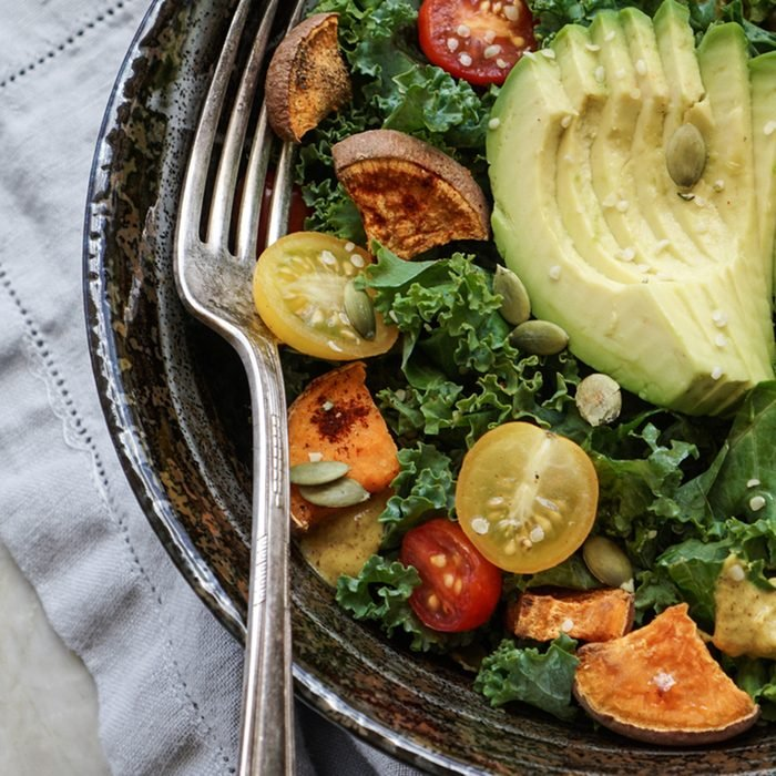 Kale, roasted yams and avocado salad on stone background
