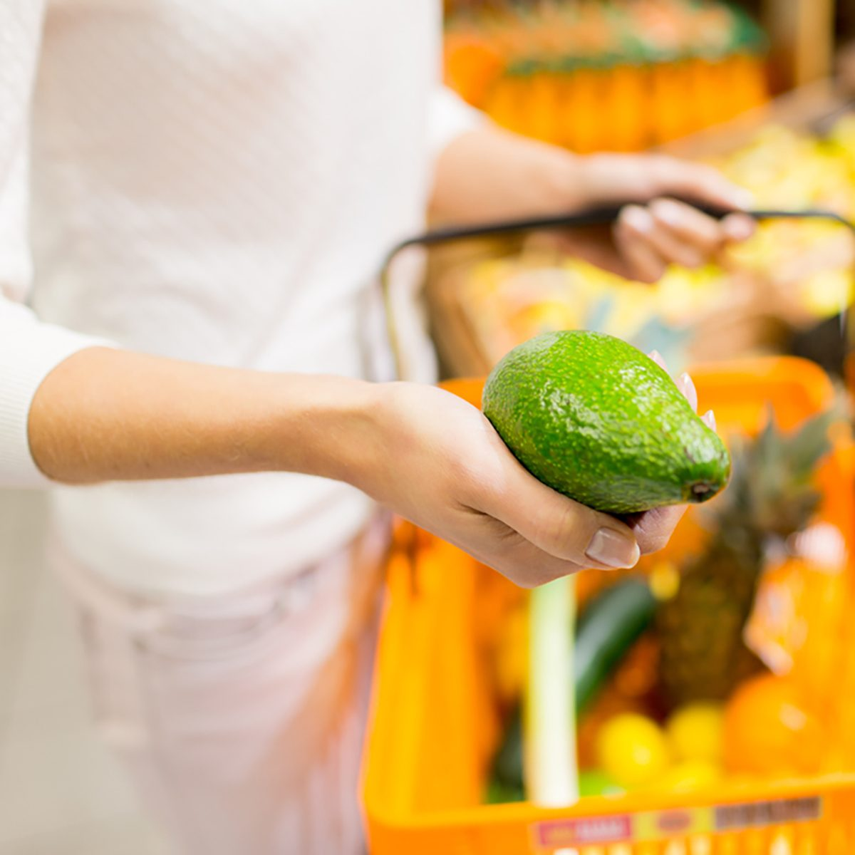 close up of young woman with food basket and avocado in market