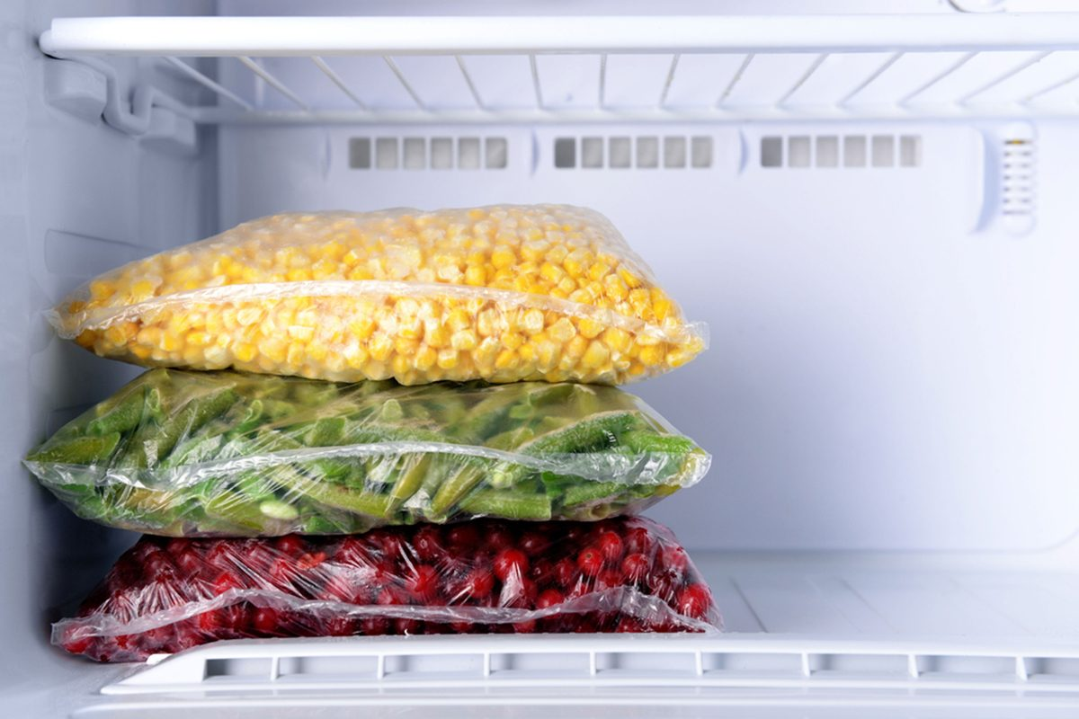 Frozen berries and vegetables in bags in freezer close up; Shutterstock ID 280873502