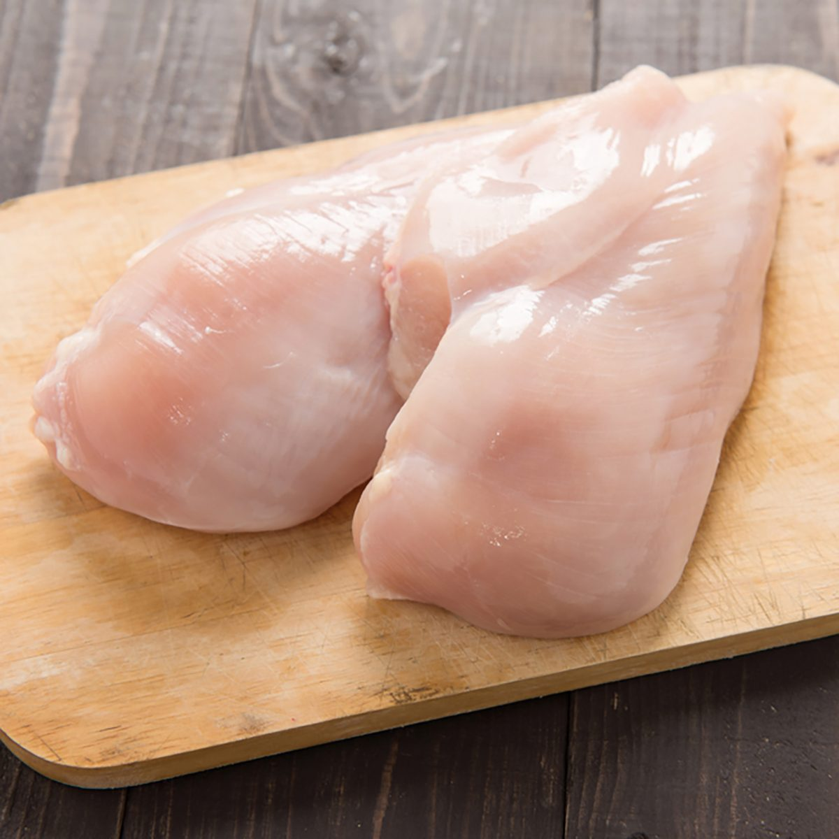 Raw chicken breast fillets on wooden background