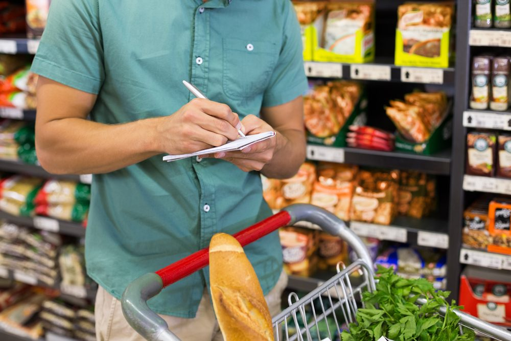 Man writing in his notepad in aisle at supermarket; Shutterstock ID 297263261