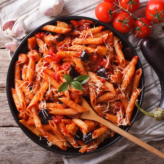 Italian food: Pasta alla Norma close-up on the table and ingredients