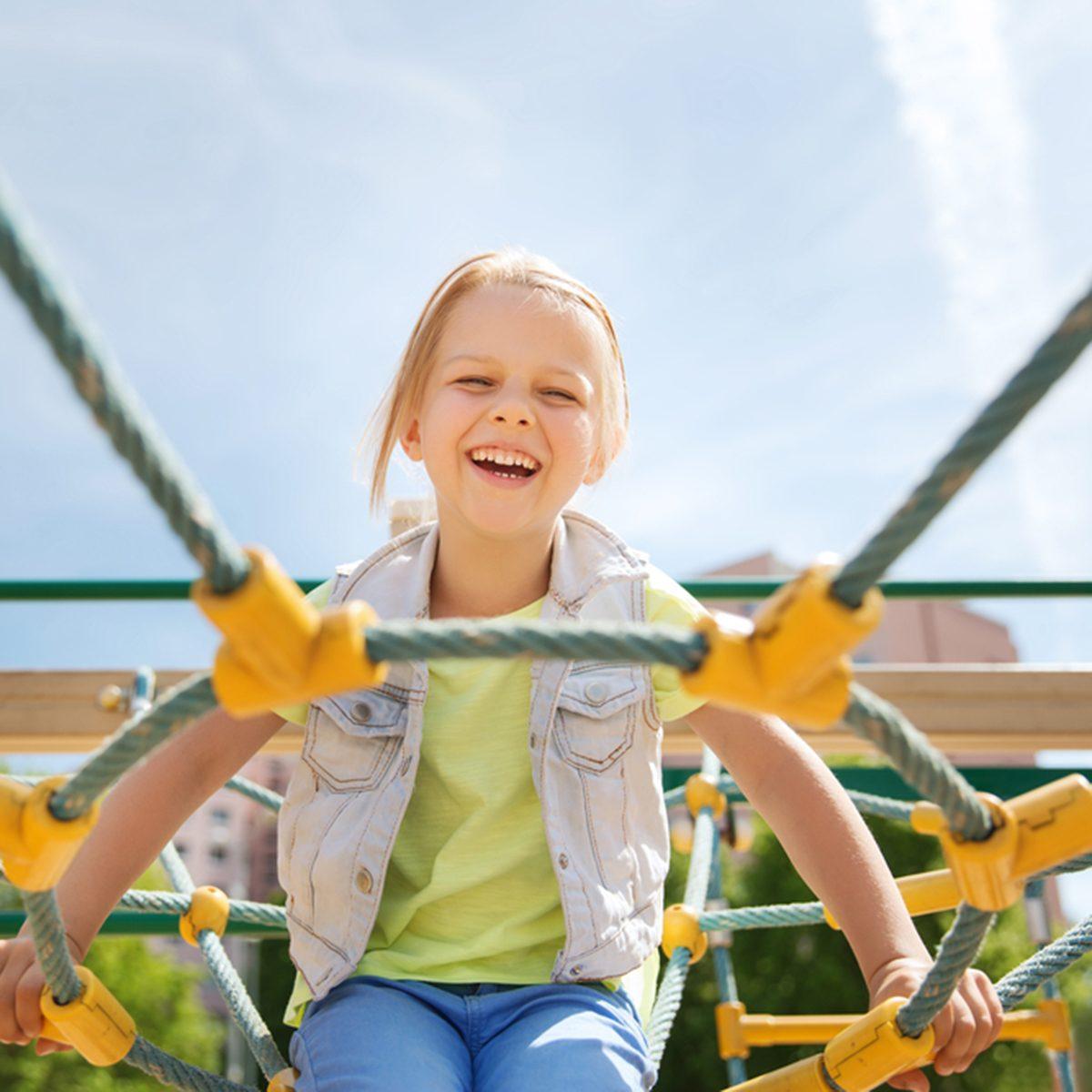 happy little girl on children playground climbing frame
