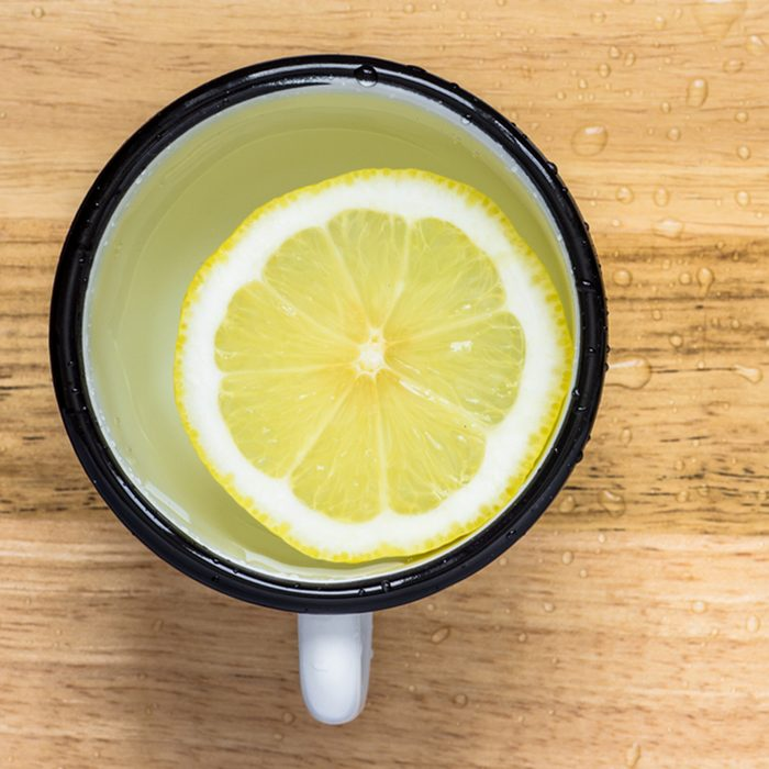 Lemon slice in water in a steel mug view from above