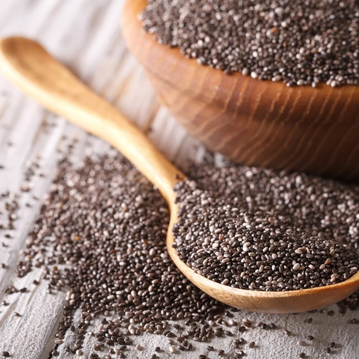 Healthy Chia seeds in a wooden spoon on the table close-up. horizontal