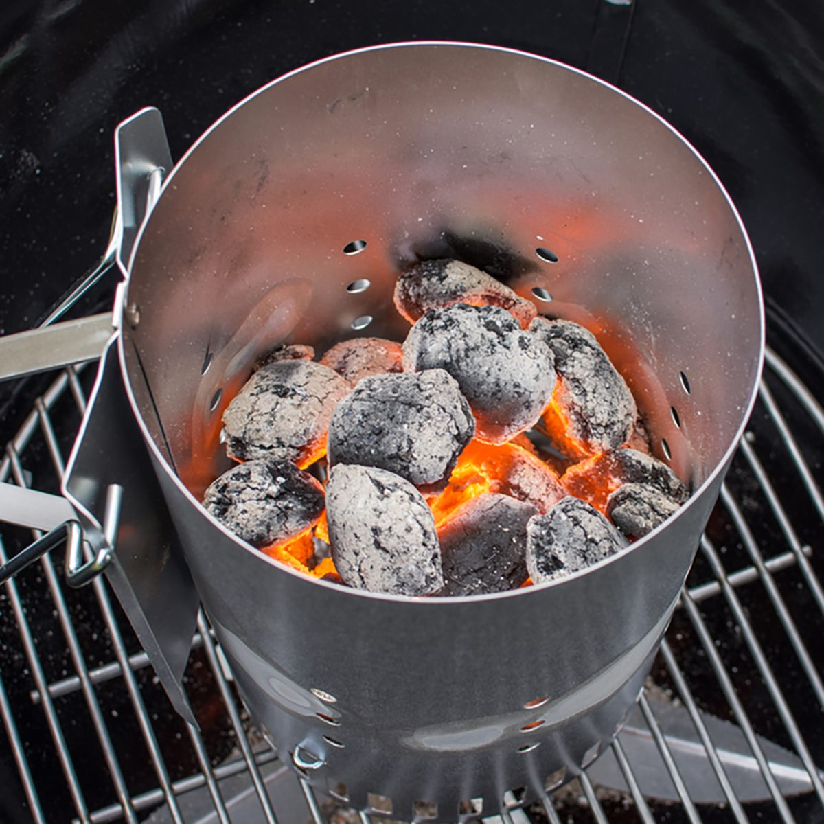 Flaming hot charcoal briquettes in a grill starter;