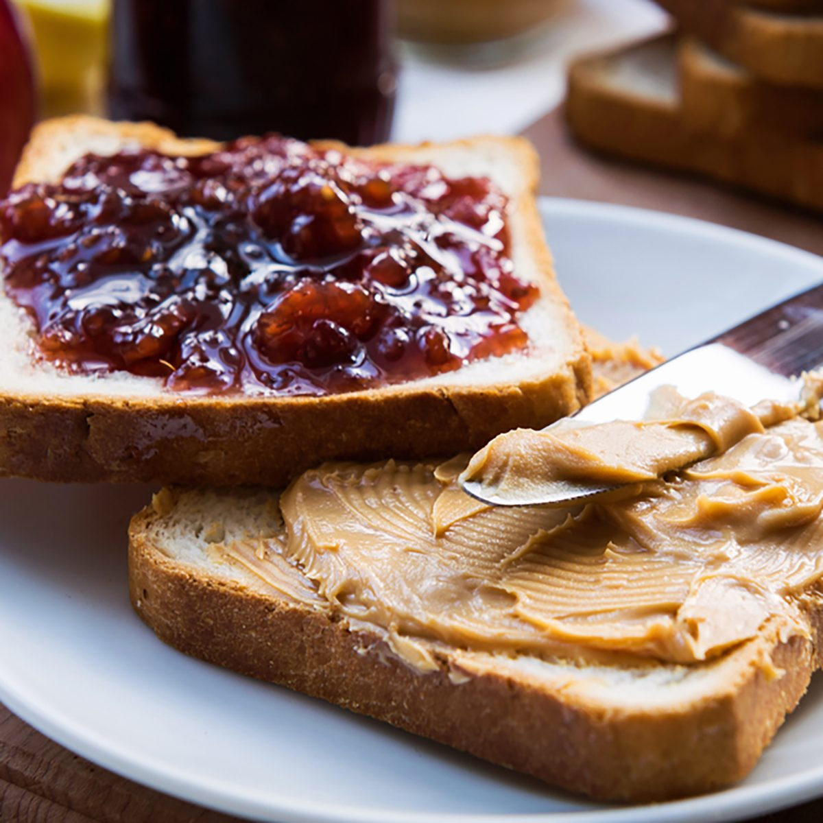 Peanut butter and raspberry jelly sandwich on wooden background.