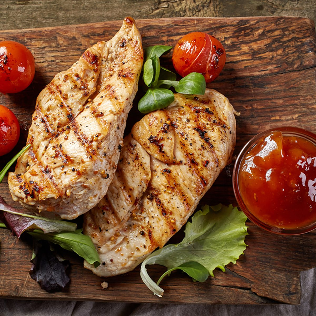 grilled chicken fillets on wooden cutting board