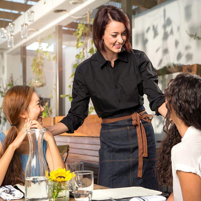 Friendly waiter server laughing smiling having fun with customer patron