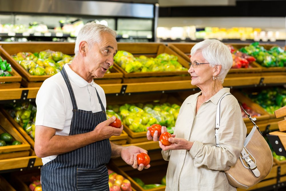 Senior customer and worker discussing vegetables in supermarket; Shutterstock ID 388529230; Job (TFH, TOH, RD, BNB, CWM, CM): TOH Grocery Shopping Secrets