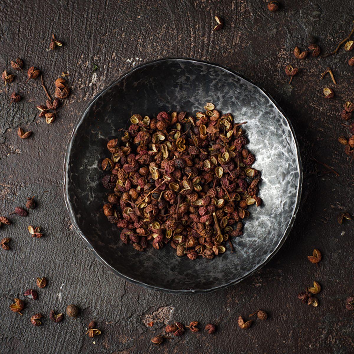 Szechuan peppercorns - Sichuan pepper in metal bowl on dark background. Selective focus