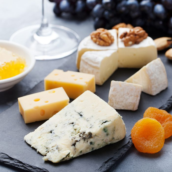Assortment of cheese with honey, nuts and grape on a modern cutting board slate background