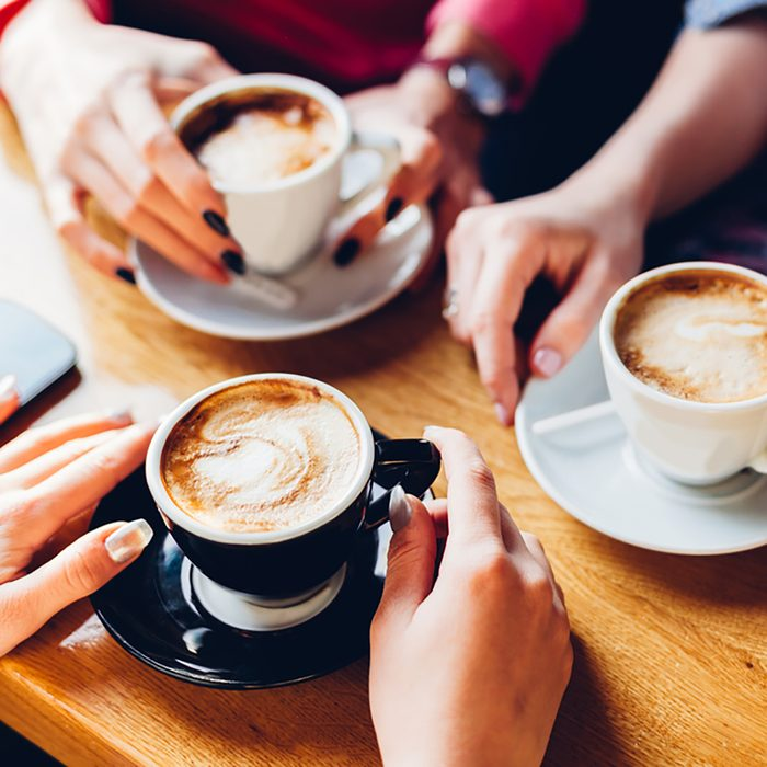 Closeup of hands with coffee cups in a cafe