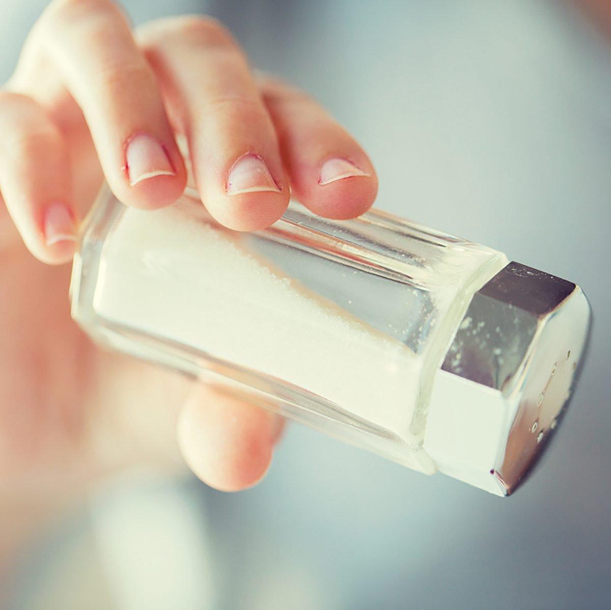 close up of hand holding white salt