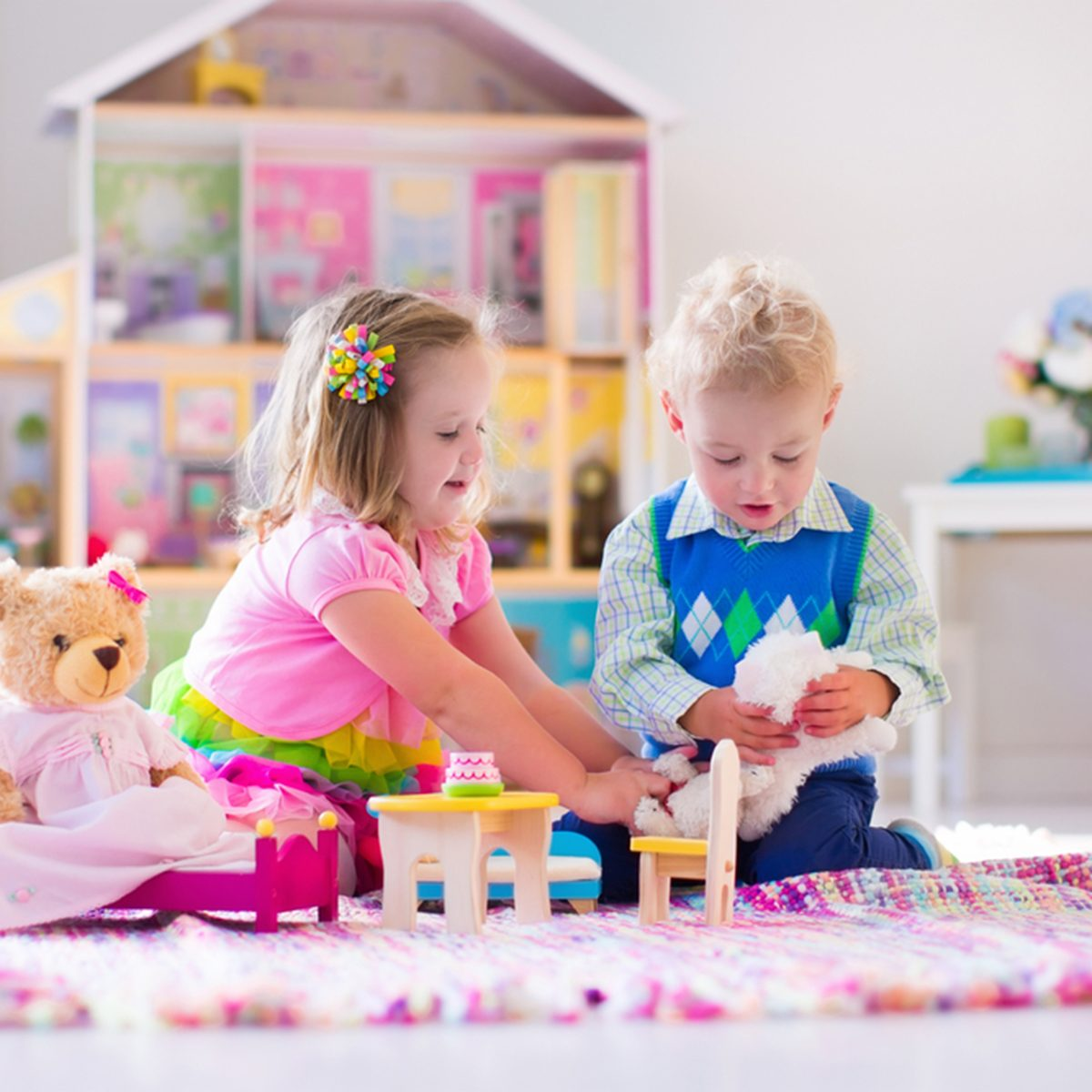 Kids playing with doll house and stuffed animal toys.