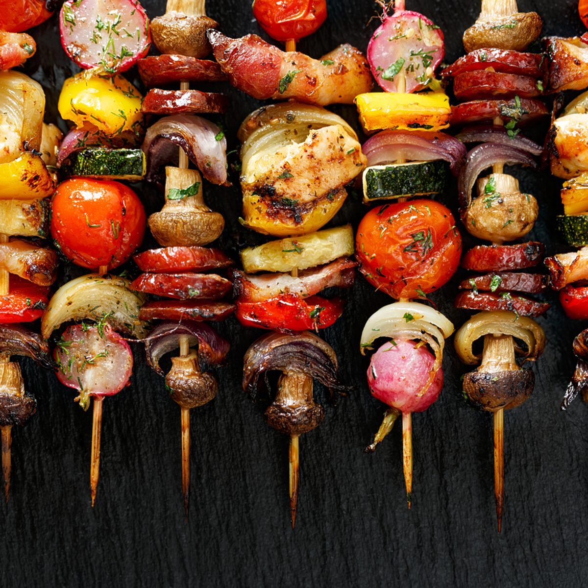 Grilled vegetable and meat skewers on the black stone background