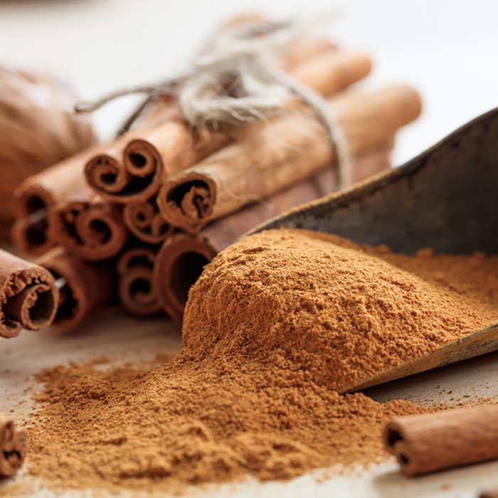 Cinnamon sticks and powder on a wooden table.