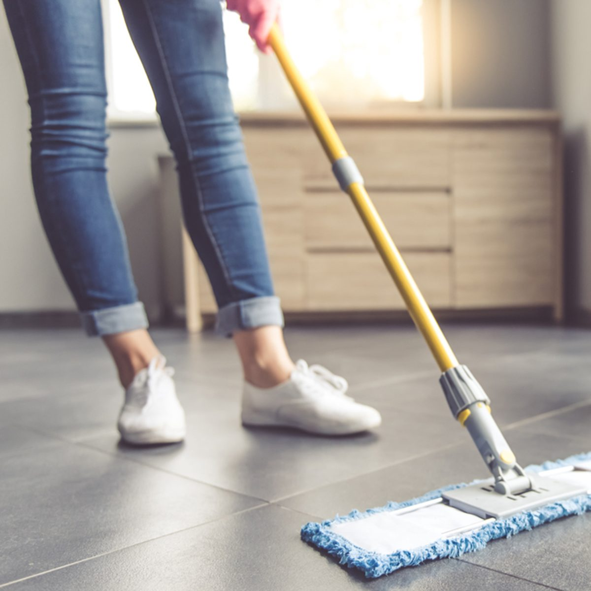 Cropped image of beautiful young woman in protective gloves using a flat wet-mop while cleaning floor in the house; Shutterstock ID 510917479
