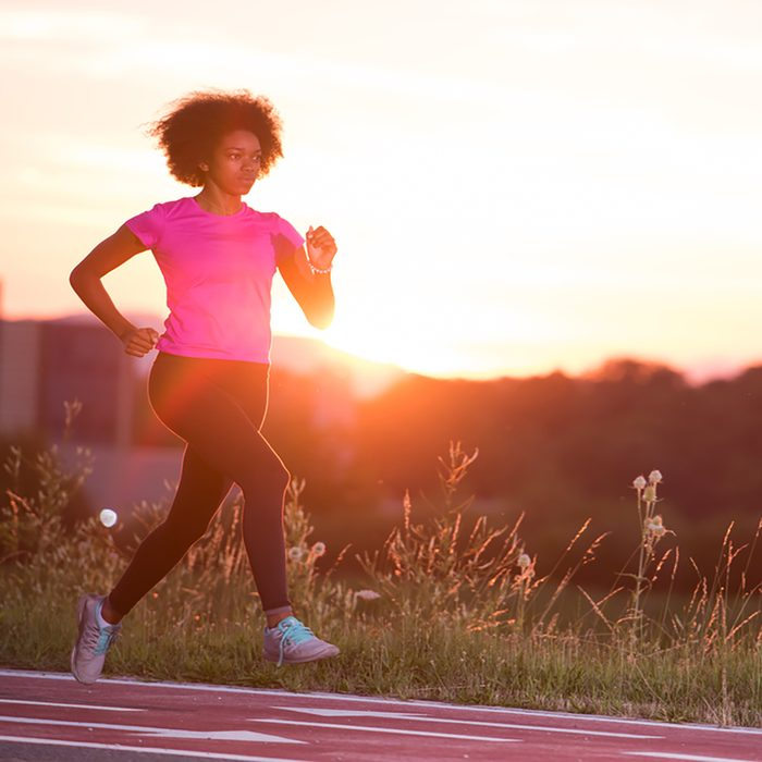 young beautiful African American woman enjoys running outside beautiful summer evening in the city