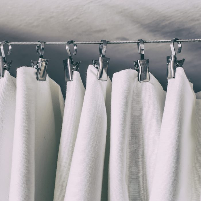 cream-colored curtain hanging on a string on a metal hook in white ceiling illuminated by daylight