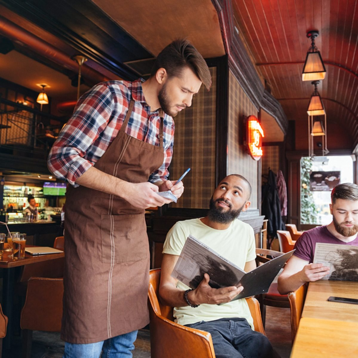 Serious concentrated young waiter standing and taking an order from two bearded handsome men in cafe