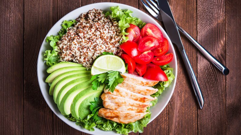 Healthy salad plate with quinoa, cherry tomatoes, chicken, avocado, lime and mixed greens, lettuce, parsley on wooden background top view