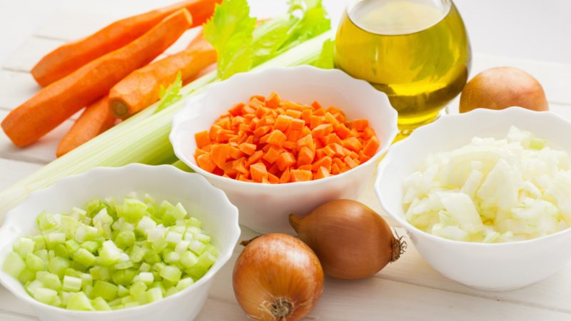 Mirepoix, chopped vegetable cut, mixture of onion, carrot and celery with olive oil on the white wooden table, horizontal