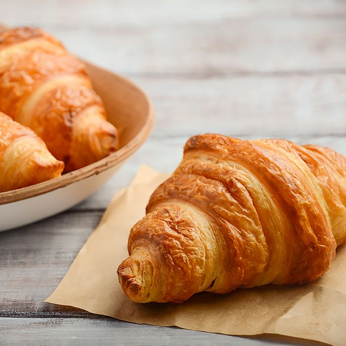 Fresh Croissants on rustic wooden background.