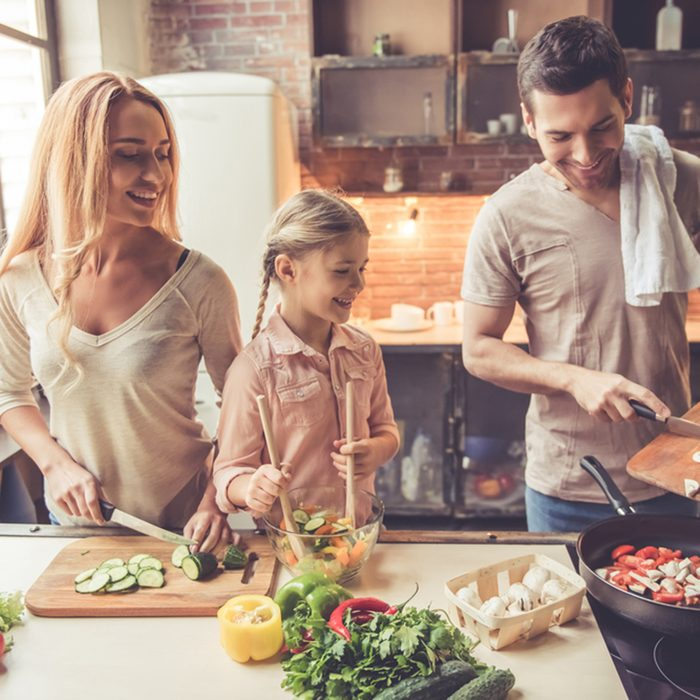 Cute little girl and her beautiful parents are smiling while cooking in kitchen at home
