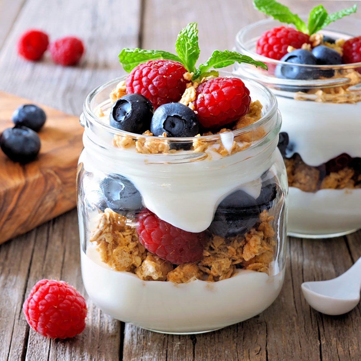 Blueberry and raspberry parfaits in mason jars,