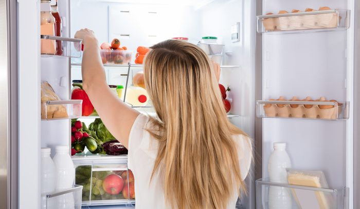 Rear View Of Young Woman Looking At Food In Open Refrigerator; Shutterstock ID 566230429